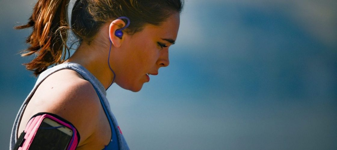 woman-wearing-smartphone-armband-and-blue-earphones-2291874
